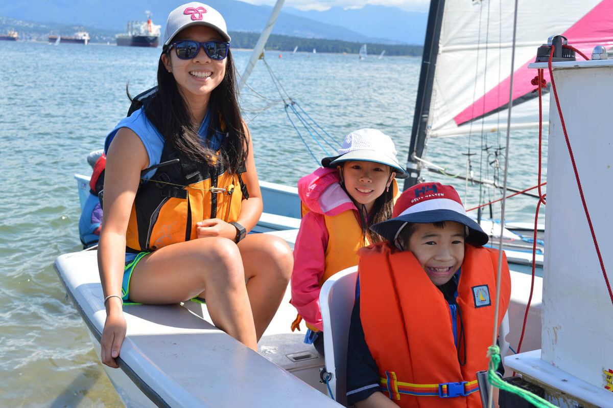 Volunteer with two young members in sail boar on kids day.